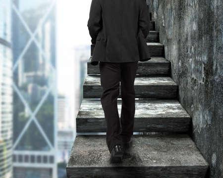 Vue arrière d'homme d'affaires à pied les vieux escaliers en béton, avec des bâtiments de la ville de fond.