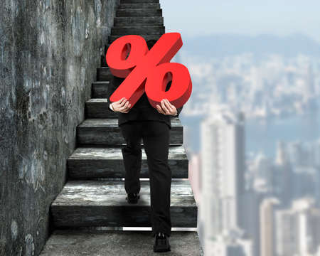 Man carrying red percentage sign climbing on old concrete stairs, with city buildings background.