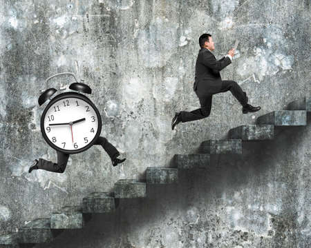 dirty old man: Alarm clock with running legs running after man holding tablet, on old dirty concrete stairs with wall background.
