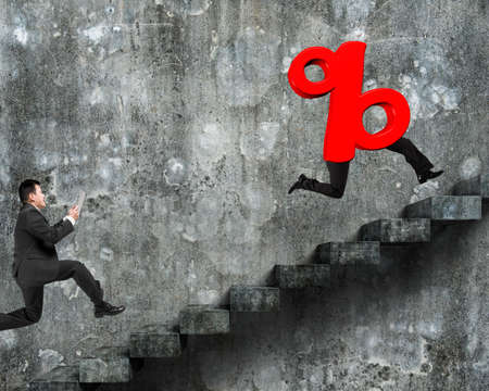 dirty old man: Man running after 3D red percentage sign with human legs, on old dirty concrete stairs with wall background.