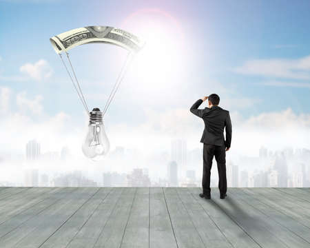 gazing: Businessman gazing light bulb with money parachute, on city buildings background.