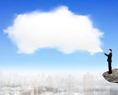 copy sapce: Man spraying white cloud paint standing on cliff. Stock Photo