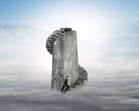 Businessman climbing old dirty concrete spiral staircase tower over cloudscape background. Stock Photo