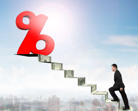 percentage sign: Man walking up toward 3D red percentage sign on top of money stairs.