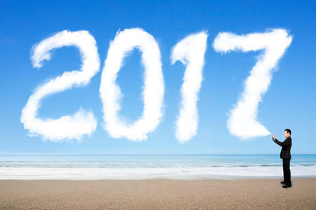 turn of the year: Businessman spraying white 2017 year cloud shape in blue sky on sea beach background. Stock Photo