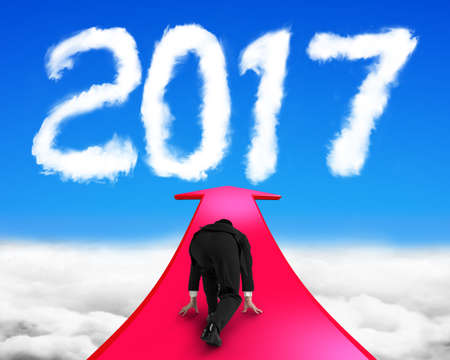 Businessman ready to run on red arrow going upward, toward white 2017 year shape clouds in blue sky.