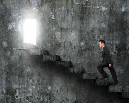 Businessman climbing old concrete stairs toward open door with bright light.