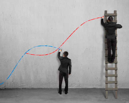 population growth: The second curve concepts, two men holding chalk drawing curves on concrete wall. Stock Photo