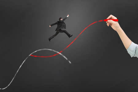 Die zweite Kurve Konzepte, Frau Hand, die Kreide zwei Kurven mit Geschäftsmann Springen zeichnen. Standard-Bild