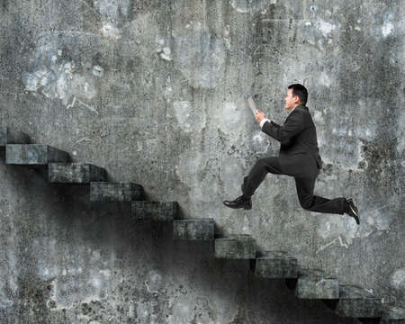 dirty old man: Man using tablet running on old dirty concrete stairs with wall background.