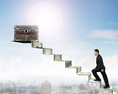 Businessman climbing spiral staircase toward old treasure chest on top of money stairs, with sunny sky city buildings background.