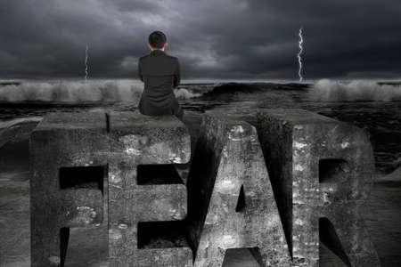 Homme d'affaires assis sur le vieux mot de peur concrète, face à l'océan tempête sombre. Banque d'images