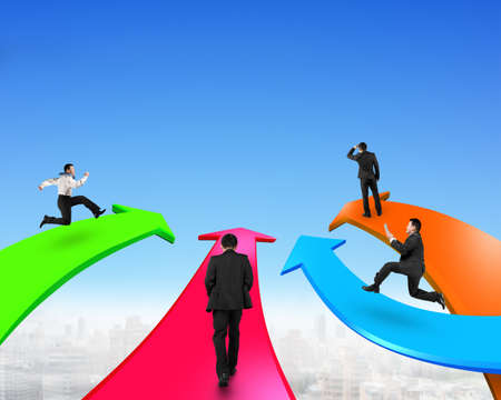 toward: Men on four color arrows go forward in the blue sky background