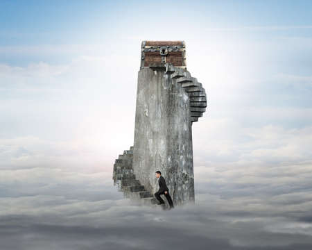 abundance: Businessman climbing spiral staircase toward old treasure chest on top of concrete tower over cloudscape background.