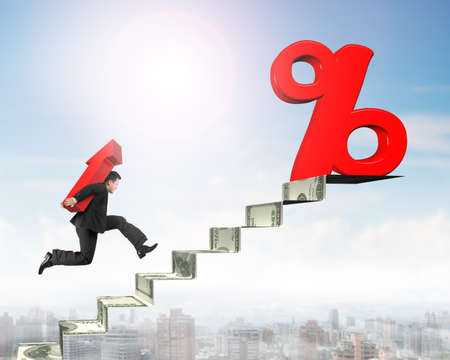 Man carrying arrow up symbol and running toward 3D red percentage sign on top of money stairs.