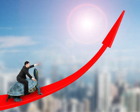 Businessman with pointing finger gesture riding turtle on red arrow up, on sun sky cityscape background. Stock Photo
