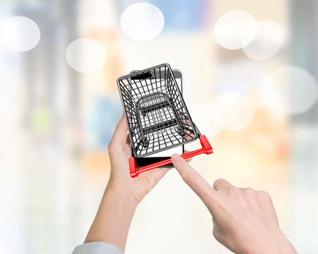 On line shopping concept. Woman forefinger pushing small shopping cart on smartphone of white screen, high angle view.