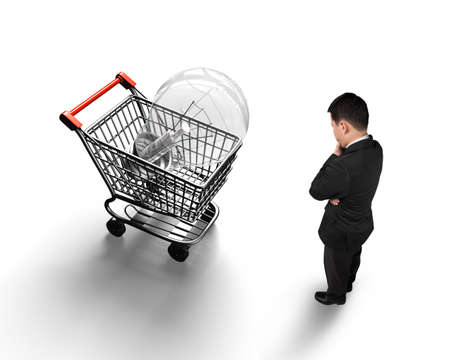 pondering: Standing man looking at shopping cart with large light bulb, isolated on white background, high angle view.