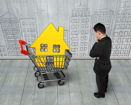 Standing man looking at golden house in shopping cart, on doodles wall and wooden floor background.