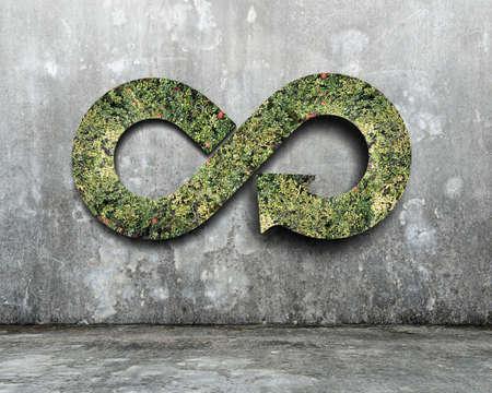 녹색 원형 경제 개념입니다. 콘크리트 벽에 잔디와 화살표 무한대 기호입니다. 스톡 콘텐츠
