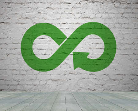 Green circular economy concept. Arrow infinity symbol with grass on brick wall.