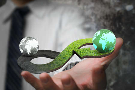 Green circular economy concept. Hand showing arrow infinity symbol with grass texture and two globes of different colors. Stockfoto