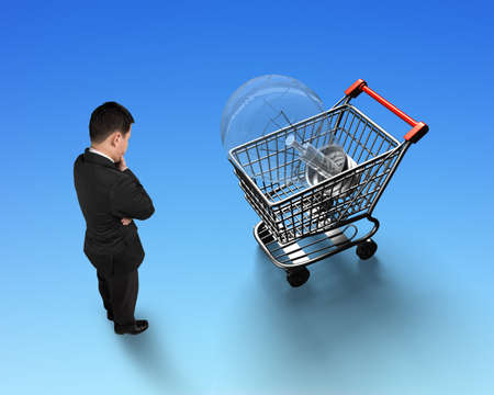 Standing man looking at shopping cart with large light bulb, isolated on blue background, high angle view. Stock Photo