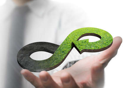 Green circular economy concept. Hand showing arrow infinity symbol with grass texture. Stockfoto