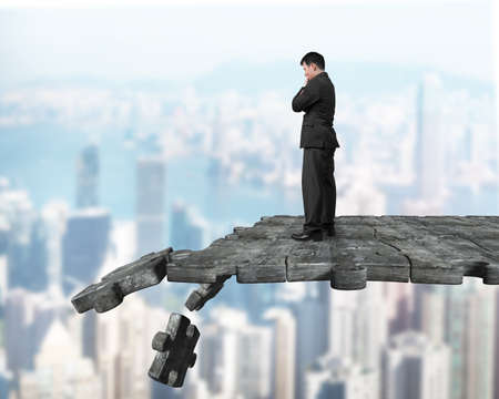 Thinking man standing on concrete puzzle ground with some pieces falling. Stock Photo