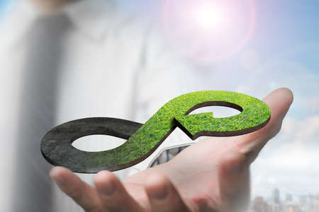 Green circular economy concept. Mans hand showing arrow infinity symbol with grass texture.