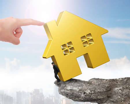 rent index: Man holding golden house on cliff edge with another big hand pushing.