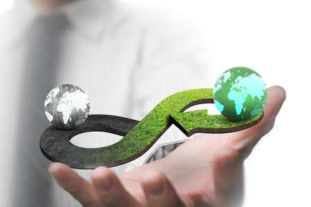 녹색 원형 경제 개념입니다. 사람의 손을 보여주는 화살표 무한대 기호 잔디 질감과 서로 다른 색상의 두 글로브.