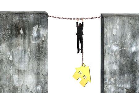 fetter: Businessman shackled by gold house hanging on iron chains connected two concrete walls, isolated on gray background.