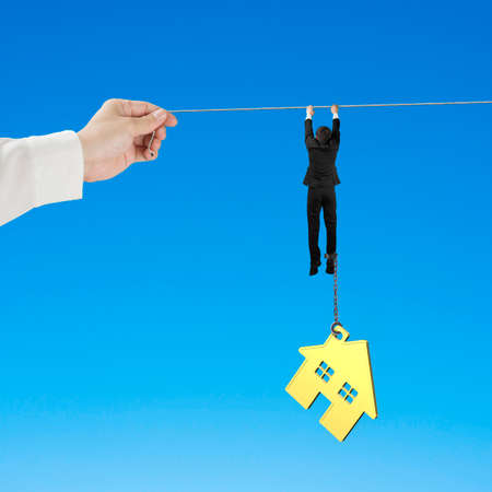 Businessman shackled by gold house hanging on the rope with big hand holding, isolated on blue background. Stock Photo