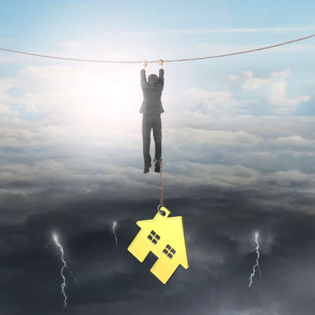 shackled: Businessman shackled by gold house hanging on the rope, on opposite weather conditions sky background, bright sun cloudscape and dark cloudy lightning. Stock Photo