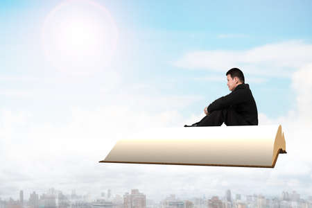 Man sitting on book flying over city in sky, side view.