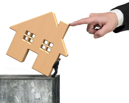 rent index: Man holding wooden house at edge of high concrete wall with another big hand helping to stop falling, isolated on white background. Stock Photo