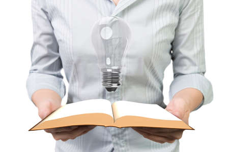 Woman hands holding the open book with light bulb, front view, isolated on white.