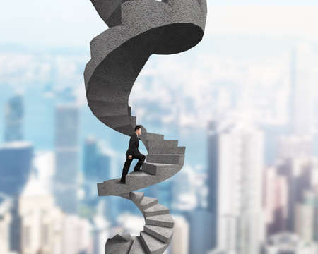 Businessman climbing concrete spiral staircase, on city skyscraper background.