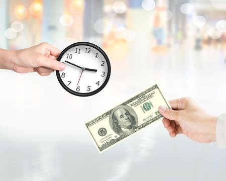 Zeitkonzept kaufen. Übergeben Sie das Halten der Dollarbanknote, um Uhr von einer anderen Handholding zu kaufen. Standard-Bild