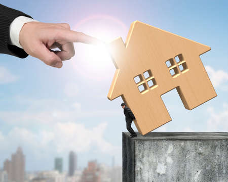 rent index: Man holding wooden house at edge of high concrete wall with another big hand helping to stop falling. Stock Photo