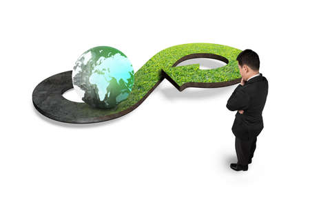 economic cycle: Green circular economy concept. Man looking at arrow infinity symbol with grass texture and colorful globe, isolated on white.