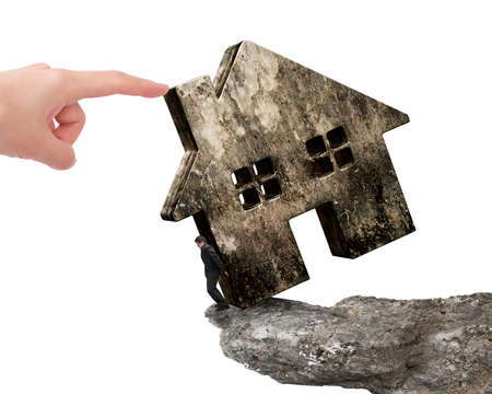 rent index: Man holding old dirty concrete house on cliff edge with another big hand pushing, isolated on white background.