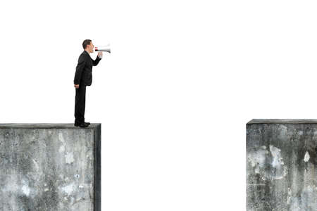 bawl: Man using megaphone yelling on top of high concrete wall, isolated on white. Stock Photo