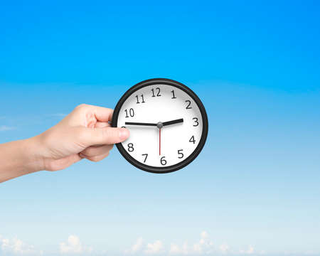 hands  hour: Hand putting a black-white clock. Time is money concept. Stock Photo