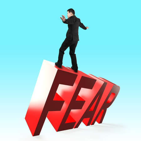 Businessman balancing on 3D red FEAR word falling. Concept of courage, overcoming fear and adversity. Stock Photo