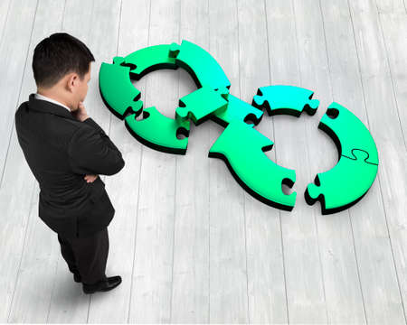 Circular economy concept. Thinking businessman looking at blue green arrow infinity symbol of jigsaw puzzle separated in small pieces, standing on wooden floor, high angle view.