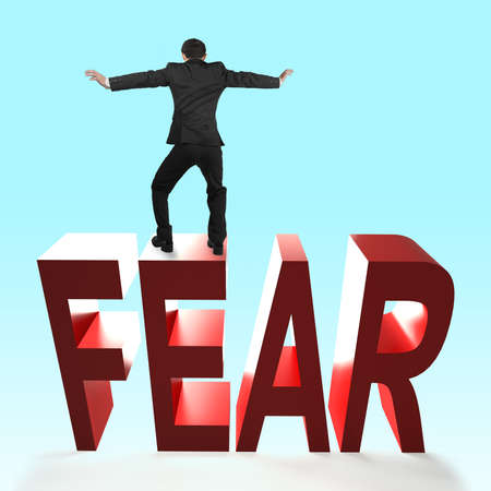 Rear view of man balancing on 3D red FEAR word falling. Concept of courage, overcoming fear and adversity.
