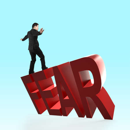 Man balancing on 3D red FEAR word falling. Concept of courage, overcoming fear and adversity. Stock Photo