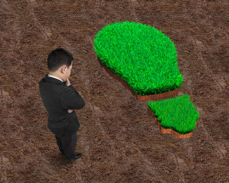 Standing businessman pondering over the green grass of light bulb on red soil background, concept of ECO and green renewable energy.